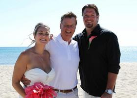 couple posing with wedding officiant