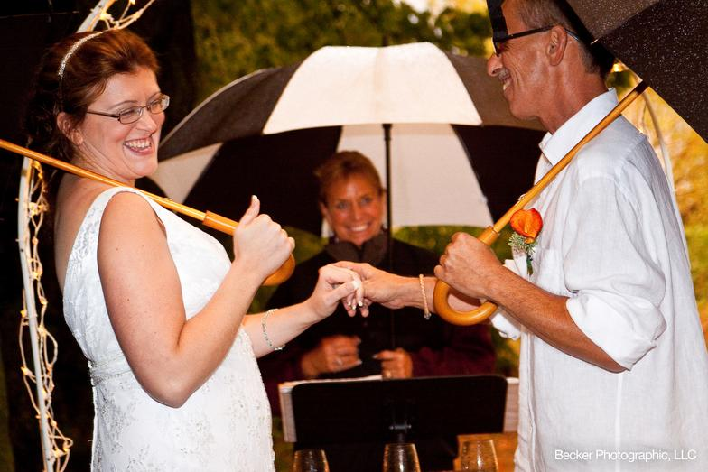 bride and groom holding umbrellas during wedding ceremony