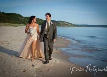 bride and groom walking on elberta beach