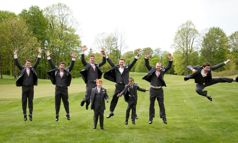 groomsmen jumping in field