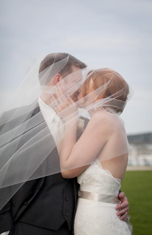 bride and groom kissing while under viel