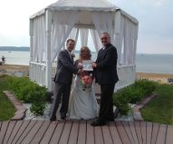 officiant, bride, and groom in front of pegoda