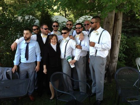 wedding officiant with groomsmen under tree