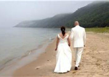 bride and groom walking along harbor bay